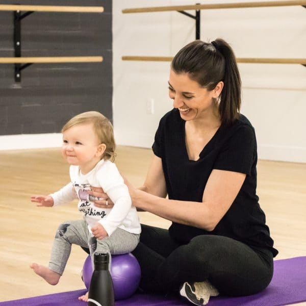 Mom sitting on yoga mat and bouncing toddler on small exercise ball