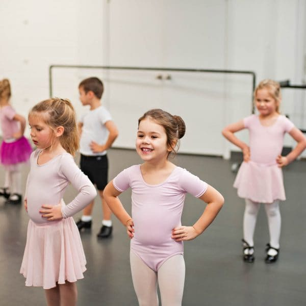 young tap dancers standing in row smiling